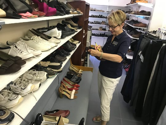 Volunteer Anne Klein inventories shoes in the clothes