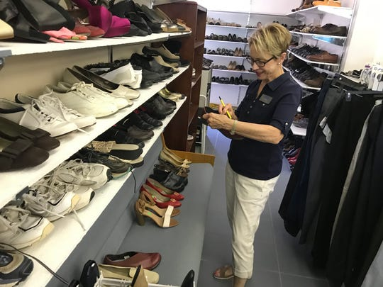 Volunteer Anne Klein inventories shoes in the clothes closet.