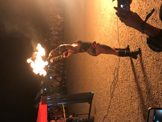 A performer at the rally holds up a pair of fire torches.