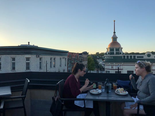 Two women enjoy dinner on the rooftop of Taylor's Peoples