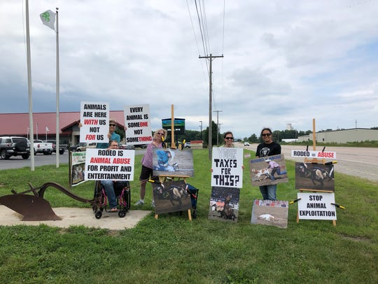 Protesters hold up signs opposing the kids' rodeo held