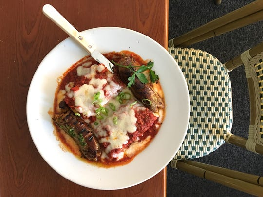 A lunch special featuring polenta baked with meat sauce and mozzarella and served with Italian sausage is seen at Roma Italian Deli & Restaurant in Newbury Park. The longtime restaurant is changing hands in early August.