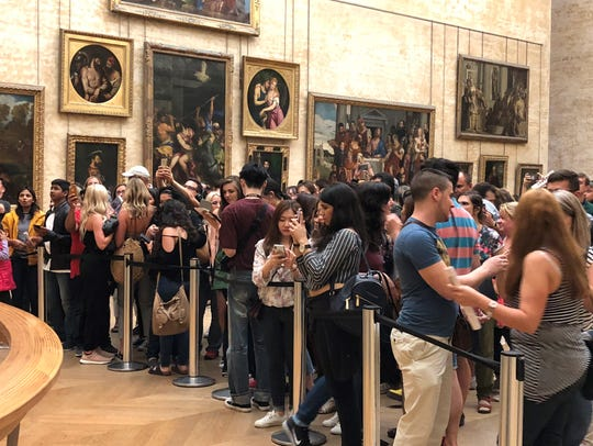Patrons of the Louvre Museum in Paris take photographs