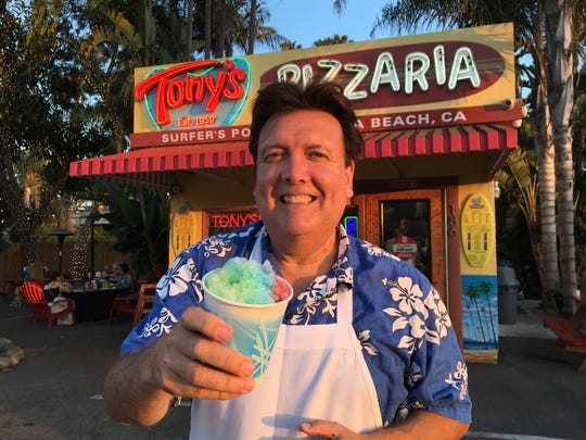"Bruce Barrios, son of late Tony's Pizzaria founder Johnny ""Tony"" Barrios, poses in front of the family-owned pizza shack with a Hawaiian shave ice. ""We're doing it the same way Dad did, with a scoop of vanilla ice cream at the bottom as a surprise for the kids,"" says Barrios."