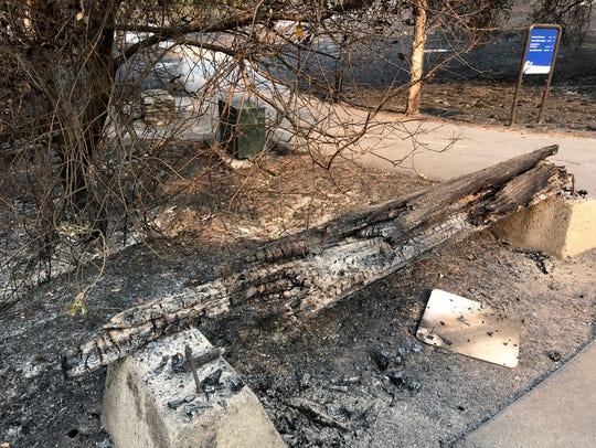 A burned wooden bench sits in front of the Sacramento