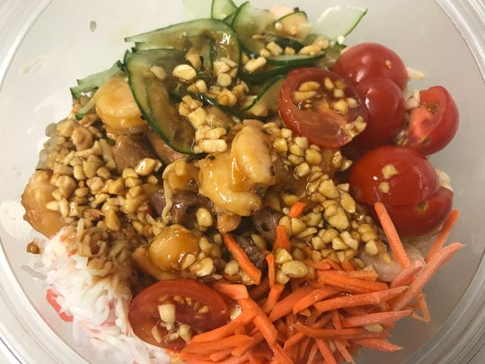 The Surf N Turf, from Poke3, has brown rice, steak and shrimp, teriyaki, cucumber, cherry tomatoes, carrots, crab salad and peanuts.
