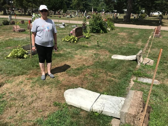 Susan Kroeplin of Wausau stands next to the damaged headstone of her great-great grandmother Ernestine Boettcher, who died in 1893. It was among 116 gravesites vandalized at Merrill Memorial Park and St. Francis Catholic cemeteries sometime between Friday, July 27, and Saturday, July 28, 2018, police said.