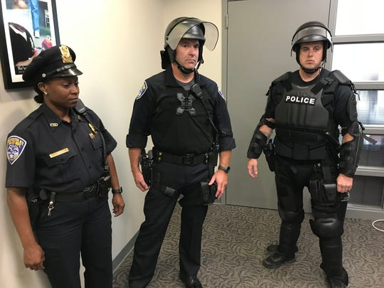 RPD Investigator Jackie Shuman, Officer Bryan Trombley (center), and Officer Jonathan Kent showing different levels of protective gear.  Shuman is in a standard uniform, and Trombley is wearing a flame retardant shirt and helmet, and Kent is wearing the full set of personal protective gear.