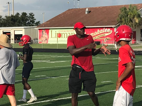 Immokalee football coach Rodelin Anthony instructs his team during a break in drills on the first day of practice Monday, July 30.
