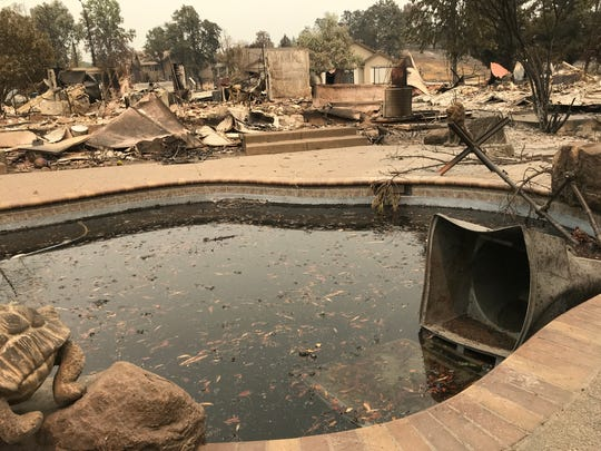 At least 16 homes were casualties on Spinnaker Drive off Old Lantern Drive in west Redding. A swimming pool at one home leveled on Spinnaker was dark with ash and leaves and a trash cart was partially submerged.