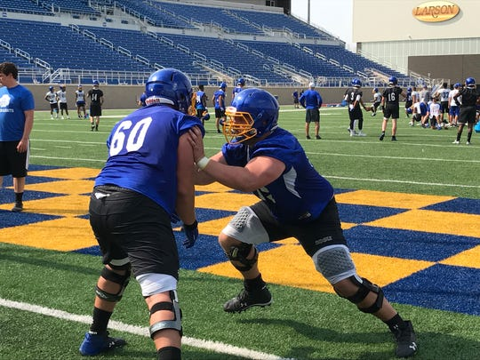 Mason McCormick (60 and Grant Schmidt work on a pass blocking drill
