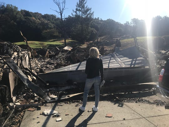 Paula Lindsay stands before the remains of her home after fires ripped through Santa Rosa last October. Her car is visible just past the garage door.