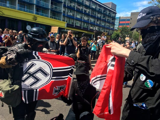 """Counter protesters tear a Nazi flag, Saturday, Aug. 4, 2018 in Portland, Ore. Small scuffles broke out Saturday as police in Portland, Oregon, deployed """"flash bang"""" devices and other means to disperse hundreds of right-wing and self-described anti-fascist protesters. (AP Photo/Manuel Valdes)"""