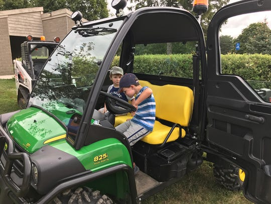 Children enjoy sitting in a vehicle at Delta Township's