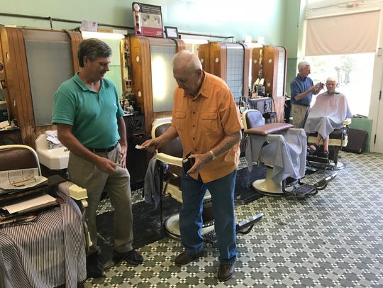 John Aspray pays Tommy Fulbright for a haircut at Dunean