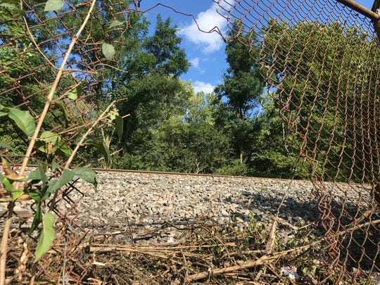 Behind a shopping plaza on Dixie Highway in Hamilton and over the railroad tracks is a homeless camp. On Wednesday, a man used this hole in the fence to get to it.
