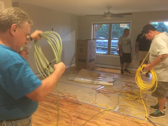 Volunteer workers clear cords in the living area of Josie Knight and Marlene Henley's house in Greenbrier on Aug. 29.