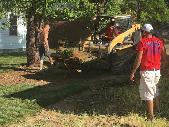 Crews install sod and finish up landscaping outside Josie Knight and Marlene Henley's house in Greenbrier.