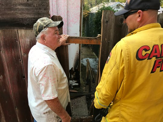 Larry Hasler of Shasta Lake shows a firefighter with the California Department of Forestry and Fire Protection where a home next door to Hasler's was damaged by fire Tuesday.