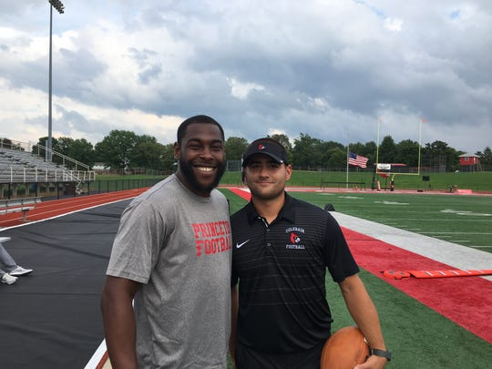 Former Colerain quarterback Dominick Goodman, who know coaches for Princeton, smiles with former Anderson quarterback Daniel Rod who coaches for Colerain.
