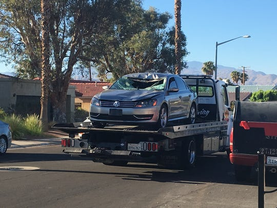 A tow truck removes a Volkswagen Passat involved in a hit-and-run Tuesday morning in Palm Springs. The driver is accused of fleeing after hitting a pedestrian on Vista Chino.