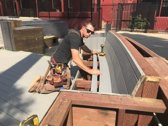 Billy Reed of Reed Construction works on a bench at