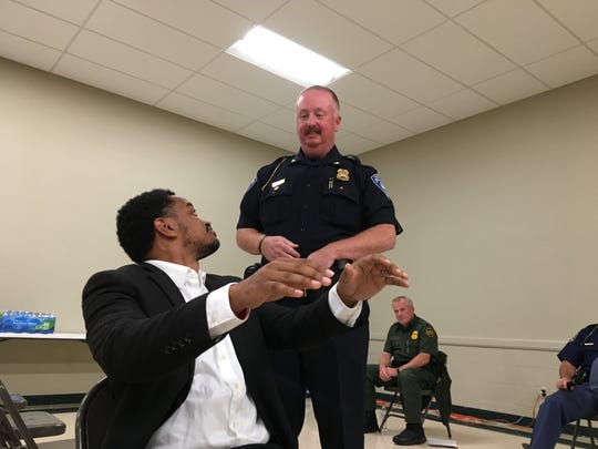 Tray Smith, left, mimics what to do when police pull you over with Port Huron Police Chief Joe Platzer during a Port Huron NAACP event Monday, Oct. 1, 2018.