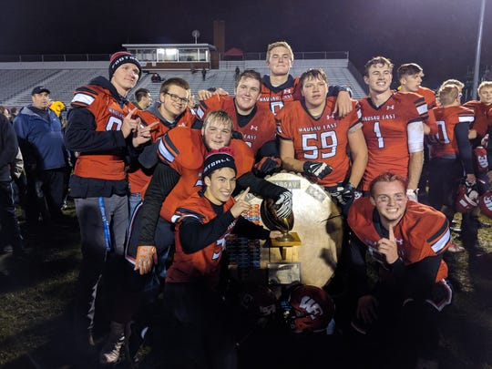 Members of the Wausau East football team are all smiles after regaining the Log trophy for the first time since 2012 with a 14-7 win over Wausau West on Friday night at Thom Field.