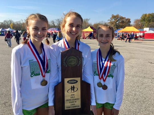 Bishop Brossart senior Ashley Beck holds the state championship trophy with Maria Klocke, left, and Amy Klocke, right.