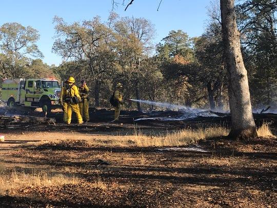 Crews mop up a vegetation fire near the corner of Browning