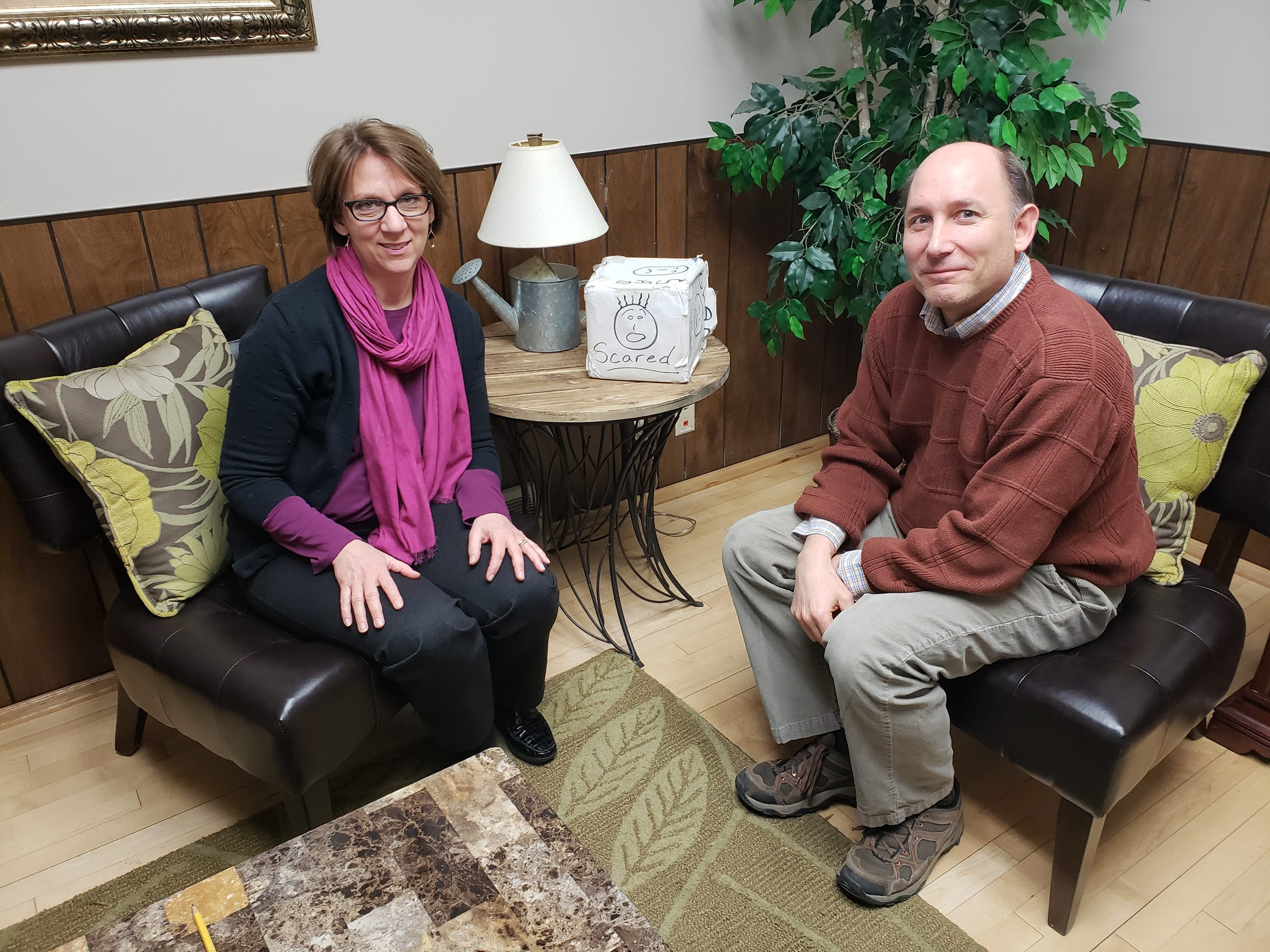 "Sue Volkman and Patrick Fendt of The Parenting Network sit next to an ""emotion box."""