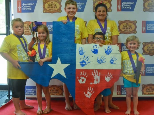 Children from the American Cancer Society's Little Baron's Ball, held at Beamers Sunday, Sept.24. The childhood cancer survivors placed their hand prints on the wooden cutout of the state of Texas, which will be auctioned off at the Cattle Baron's Ball, Saturday, Oct. 14.