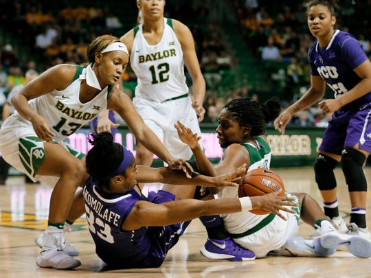 Baylor's Nina Davis (13) and Khadijiah Cave, right, scramble with TCU's Adeola Akomolafe (33) for control of a ball in the second half of an NCAA college basketball game Jan. 11, 2017, in Waco, Texas.