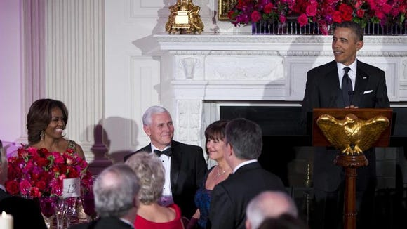 First lady Michelle Obama, left, and Gov. Mike Pence, R-Ind., center, look on as President Barack Obama delivers remarks during a dinner for the National Governors Association in the State Dining room of the White House on Sunday, Feb. 23, 2014, in Washington.