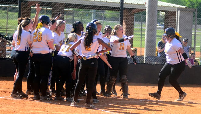 Hendersonville High teammates greet senior pitcher Carley Carlisle at home plate following her first-inning home run during Thursday afternoon's contest against Portland. Carlisle homered twice and also collected nine strikeouts in earning the pitching victory.