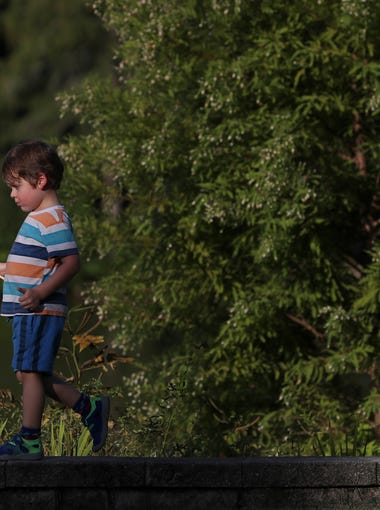 Charlie Nichols, 3, walks along the edge of Lake Ella with a rainbow flag as hundreds of people gathered for a vigil in honor of Heather Heyer, who was killed after violent protests broke out in the city of Charlottesville. The gathering featured a host of religious speakers and civic leaders, culminating with a candlelight walk around the lake.