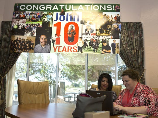Sitel Operations Manager Dorothea Martinez de Vargas, left, and Client Services Representative Malynn Smith look over documents on Tuesday, Oct. 11, 2016 in the Sitel conference room. Above them is congratulatory banner for Sitel Director John Muñoz for his 10 years leading the Las Cruces office.