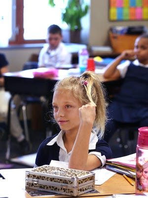 Third-grader Glynna Walters (center) and classmates listen to instructions from teacher Abby White at Irvington Community Elementary School. The school is seeking a loan through a new program for charter schools.