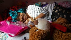 Trinity Neal lays amongst her many plush stuffed animals