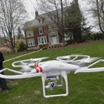 In this April 29, 2014 photo, Mark Monge demonstrates the use of the DJI Phantom 2 drone he uses to photograph homes for his work as a realtor for Jim Maloof Realty in Peoria, Ill. Monge, who sells homes with his wife Jennifer, acquired the device to photograph many area homes. (AP Photo/Journal Star, Ron Johnson)