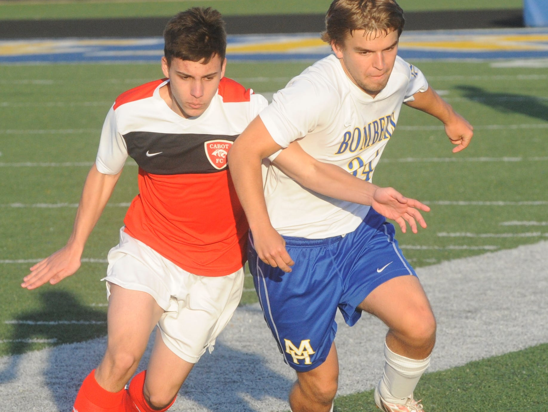 Mountain Home's Drew Hatman, right, battles a Cabot player for the ball during the Bombers' match against the Panthers on Friday night at Bomber Stadium.
