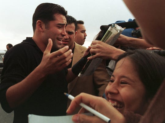 Boxing legend Oscar delaHoya signs autographs for fans after his arrival at the El Paso International Airport Tuesday morning. About 200 people came to the airport to greet the boxer who came to El Paso to promote his June bout in the Sun Bowl.