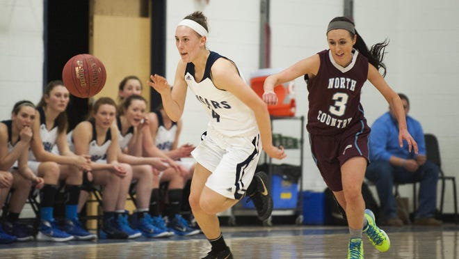 MMU's Katie Estes (14) dribbles the ball down the court during the girls basketball game between the North Country Falcons and the Mount Mansfield Cougars last season.
