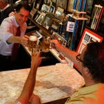 Wisconsin Gov. Scott Walker, left, Republican presidential candidate, toasts while having a beer at Chicago's Billy Goat Tavern Monday.