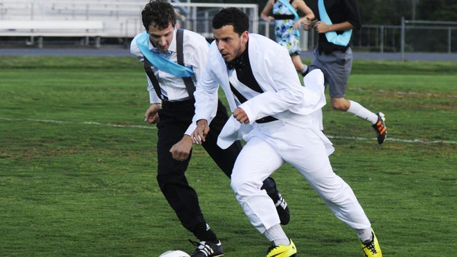 Two formally dressed opponents fight for control of the ball during last year's soccer prom.