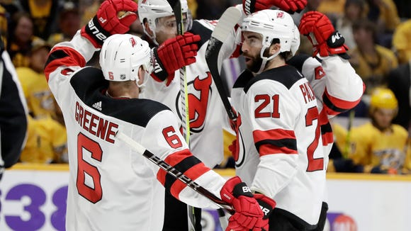 New Jersey Devils defenseman Andy Greene (6) and right wing Kyle Palmieri (21) celebrate a goal by Sami Vatanen, back right, against the Nashville Predators in the first period of an NHL hockey game Saturday, March 10, 2018, in Nashville, Tenn. (AP Photo/Mark Humphrey)