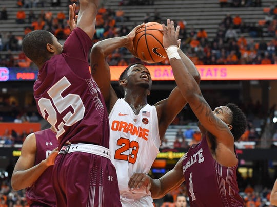 Syracuse Orange guard Frank Howard (23) drives to the basket between Colgate Raiders guard Jordan Robertson (25) and guard Jordan Burns (1) during the first half at the Carrier Dome.
