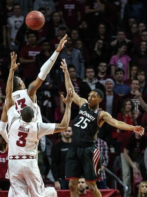 Cincinnati's Kevin Johnson throws a pass over Temple's Jesse Morgan (3) and Devontae Watson.