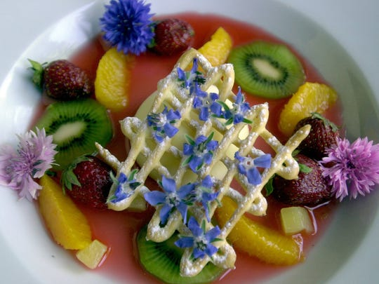 Frozen lemon custard, with fresh fruit, is topped with borage and johny jump ups.