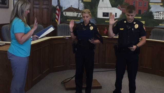 Ozark Police Officers Timothy Buie and Kelsey Cliffe raise their hands at a swearing-in ceremony on June 6.